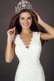 Schönes Mädchen mit dem langen Haar trägt luxuriöses Kleid und Krone Stockfoto