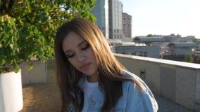 Schönes Mädchen mit dem langen Haar wirbelt Tänze in der Stadt auf einem Sonnenunterganghintergrund stock video