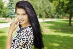 Schönes Mädchen mit dem langen schwarzen Haar mit einer glücklichen Stellung des Lächelns im Park Stockfotos
