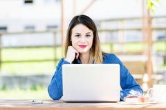 Schönes Mädchen mit dem Laptop, der in Richtung der Kamera blickt Lizenzfreies Stockbild