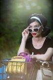 Schönes Mädchen mit dem Retro- Blick, der eine schwarze Ausstattung hat Spaß im Park mit Fahrrad trägt Lebensstilkonzept im Freie Stockfotografie