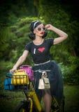 Schönes Mädchen mit dem Retro- Blick, der eine schwarze Ausstattung hat Spaß im Park mit Fahrrad trägt Lebensstilkonzept im Freie Stockfoto