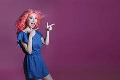 Schönes Mädchen mit dem rosa Haar im blauen Kleid zeigt Zeichen auf lila Hintergrund, Platz für Text Lizenzfreie Stockbilder