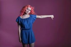 Schönes Mädchen mit dem rosa Haar im blauen Kleid zeigt Zeichen auf lila Hintergrund, Platz für Text Stockfotos