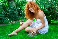 Schönes Mädchen mit dem roten Haar auf Natur mit einem Kaninchen in ihren Händen Lizenzfreies Stockbild