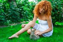 Schönes Mädchen mit dem roten Haar auf Natur mit einem Kaninchen in ihren Händen Lizenzfreie Stockbilder