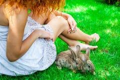 Schönes Mädchen mit dem roten Haar auf Natur mit einem Kaninchen in ihren Händen Lizenzfreie Stockfotos
