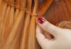 Schönes Mädchen mit dem roten Haar, Friseur spinnt eine Zopfnahaufnahme, in einem Schönheitssalon lizenzfreie stockfotografie