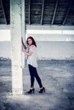 Schönes Mädchen mit dem roten Haar im Freien in geworfenem altem Lager Lizenzfreie Stockfotografie