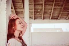 Schönes Mädchen mit dem roten Haar im Freien in geworfenem altem Lager Lizenzfreies Stockfoto