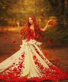 Schönes Mädchen mit dem roten Haar im Herbstpark lizenzfreie stockbilder