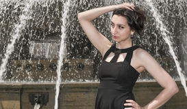 Schönes Mädchen mit dem schwarzen Kleid, das ihr Haar, alter Brunnen im Hintergrund hochhält Stockbilder