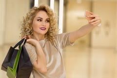 Schönes Mädchen mit den Einkaufstaschen, die ein selfie mit ihrem Handy nehmen lizenzfreie stockfotografie