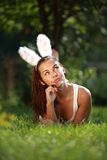 Schönes Mädchen mit den Kaninchenohren liegt auf einem Gras Lizenzfreie Stockfotografie
