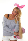 Schönes Mädchen mit den Ohren eines Rosakaninchens auf seinem Kopf Lizenzfreies Stockfoto