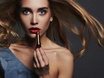 Schönes Mädchen mit den roten Lippen junge Frau, die rotes lipstic setzt Stockfoto