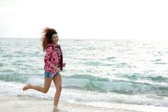 Schönes Mädchen mit der bunten Windjacke, die auf dem Strand läuft lizenzfreie stockfotos