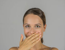Schönes Mädchen mit der Hand auf ihrem Mund Stockbild