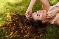 Schönes Mädchen mit der natürlichen reinen Haut, die draußen, auf dem Rasen liegt und sich entspannt Stockbilder