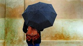 Schönes Mädchen mit einem braunen ledernen Rucksackholdingregenschirm in der Straße an einem regnerischen Tag - Besuchs-Copenaghe stockfoto