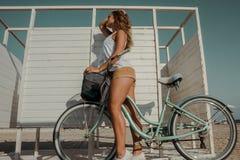 schönes Mädchen mit einem Fahrrad auf dem Strand Lizenzfreies Stockfoto