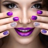 Schönes Mädchen mit einem hellen Abendmake-up und purpurrote Maniküre mit Bergkristallen Nageldesign Schönes lächelndes Mädchen stockfotos