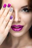 Schönes Mädchen mit einem hellen Abendmake-up und purpurrote Maniküre mit Bergkristallen Nageldesign Schönes lächelndes Mädchen lizenzfreies stockbild