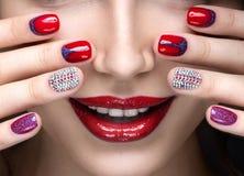 Schönes Mädchen mit einem hellen Abendmake-up und rote Maniküre mit Bergkristallen Nageldesign Schönes lächelndes Mädchen stockfoto