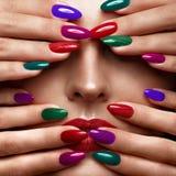 Schönes Mädchen mit einem klassischen Make-up und mehrfarbigen Nägeln Maniküredesign Schönes lächelndes Mädchen lizenzfreies stockbild