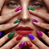 Schönes Mädchen mit einem klassischen Make-up und mehrfarbigen Nägeln Maniküredesign Schönes lächelndes Mädchen lizenzfreies stockfoto