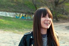 Schönes Mädchen mit einem Knall und einem langen Haar lacht in einer Weste und in einer Lederjacke lizenzfreie stockfotos