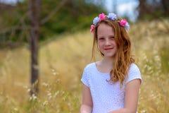 Schönes Mädchen mit einem Kranz auf ihrem Kopf auf einem Weizengebiet stockbilder