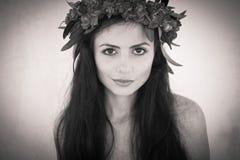 Schönes Mädchen mit einem Kranz von Blumen auf ihrem Kopf Lizenzfreie Stockbilder
