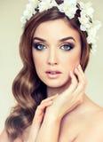 Schönes Mädchen mit einem Kranz von Blumen auf ihrem Kopf Stockfotografie