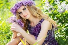 Schönes Mädchen mit einem Kranz von lila Blumen Lizenzfreie Stockfotos