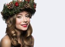 Schönes Mädchen mit einem Kranz von Weihnachtsbaumasten und -kegeln Bild des neuen Jahres Schönes lächelndes Mädchen lizenzfreies stockbild