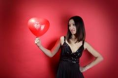 Schönes Mädchen mit einem roten Ballon in Form von h Lizenzfreies Stockfoto