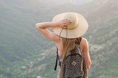 Schönes Mädchen mit einem Rucksack und einem breiten Hut, die mit ihr zurück gegen einen Hintergrund von grünen Bergen stehen Lizenzfreie Stockfotografie
