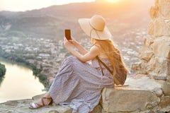 Schönes Mädchen mit einem Rucksack und in einem Hut macht Fotos des Flusses und der Stadt unten Lizenzfreie Stockfotografie