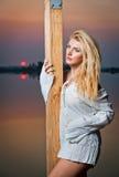 Schönes Mädchen mit einem weißen Hemd auf dem Pier bei Sonnenuntergang Lizenzfreies Stockbild