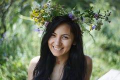 Schönes Mädchen mit einem wreat von Blumen auf ihrem Kopf Lizenzfreies Stockfoto