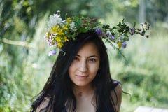 Schönes Mädchen mit einem wreat von Blumen auf ihrem Kopf Stockfotografie