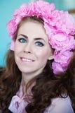 Schönes Mädchen mit einer Blume auf dem Kopf Stockfotografie
