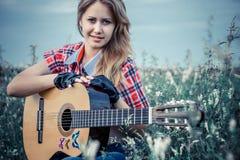 Schönes Mädchen mit einer Gitarre Stockbilder