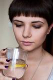 Schönes Mädchen mit einer Kurzhaarfrisur, die das kalte Wasser mit Eis und Zitrone betrachtet Stockbild