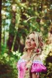 Schönes Mädchen mit einer langen Borte im rosa Spitzekleid lächelt im Wald Stockfotos