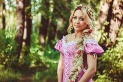 Schönes Mädchen mit einer langen Borte im rosa Spitzekleid lächelt im Wald Stockbilder