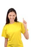 Schönes Mädchen mit gelbem T-Shirt oben zeigend. Stockfotografie