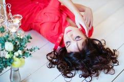 Schönes Mädchen mit geschlossenen Augen in einem roten Kleid, das auf dem floo liegt stockfoto