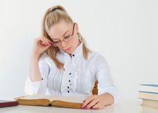 Schönes Mädchen mit Gläsern ein Buch lesend Lizenzfreie Stockbilder